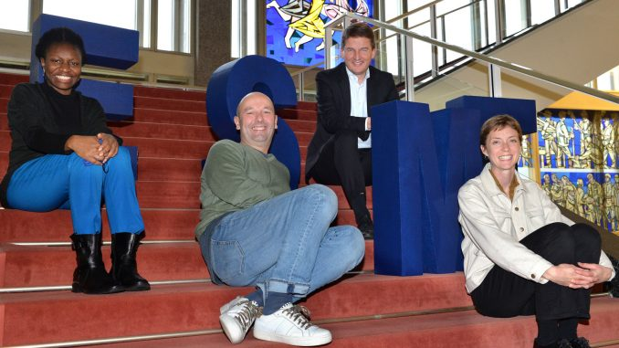 Duroseme Taylor, Harald Panzer, Jörg Rocholl and Claire Duggan sitting on stairs at ESMT Berlin