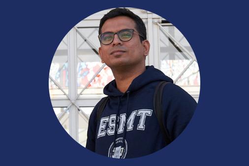 Aparajith Raman stading in front of the ESMT building wearing ESMT hoodie.