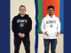 Thomas Hudson and Rashid Quddus wearing ESMT hoodies and standing beside each other with a colourful wall behind them.